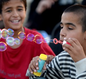 epaselect epa04937488 A migrant child blows bubbles made from soap and water while waiting at a registration camp after they crossed the border between Greece and Macedonia near the city of Gevgelija, The Former Yugoslav Republic of Macedonia, 18 September 2015. Thousands of migrants continue to arrive in Macedonia, on their way to Serbia, Croatia and EU countries. Hungary on 15 September sealed the last gap in the barricade along its border with Serbia, closing the passage to thousands of refugees and migrants still waiting on the other side.  EPA/Nake Batev