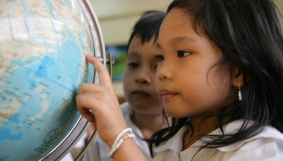 Fiona, 7, points to a globe, as a classmate watches, on the first day of school at Rosauro Almario Primary School in Tondo, a neighbourhood of Manila, the capital. UNICEF assists the 'child-friendly' school with teacher training, books and other supplies. Child-friendly schools strive to create safe, protective and inclusive spaces for all children, especially girls, and encourage the involvement of parents and the community.  In 2006 in the Philippines, HIV transmission is hidden and growing. While official statistics cite fewer than 10,000 HIV cases nationwide, high-risk behaviours, especially among adolescents, are on the rise. Those at highest risk are children in depressed, urban areas, those who live or work in the streets and those involved in the sex industry. Many have limited access to basic services like education, community support and health care. And a strong culture of stigma, denial and silence has prevented an open discussion of HIV/AIDS, sexuality and adolescent reproductive health. Other factors impeding prevention and care services include limited knowledge and skills among health-care workers; rapid turnover and migration of staff; and disruption of health systems due to emergencies and conflict. On Mindanao Island, a decades-long conflict between Christians and Muslims has killed, injured or displaced thousands of children, and left others vulnerable to abduction, trafficking and abuse. Working with government, NGO and other partners, UNICEF supports peer counselling and prevention awareness training for adolescents; expanded voluntary counselling and testing services; and treatment, care and support services for children infected with HIV/AIDS. UNICEF also supports child protection, peace building and the delivery of social services in conflict areas.